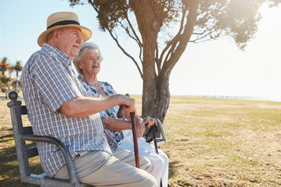 elderly couple sitting together on a bench outside in the sun